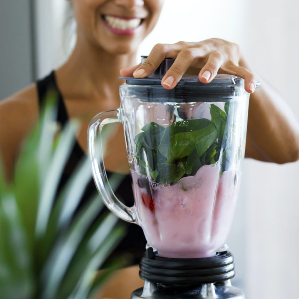 Nutritional Wellbeing-smiling woman making healthy smoothie in blender